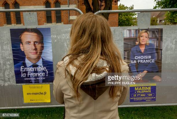 A woman looks at election campaign posters for French presidential election candidate for the farright Front National party Marine Le Pen and...
