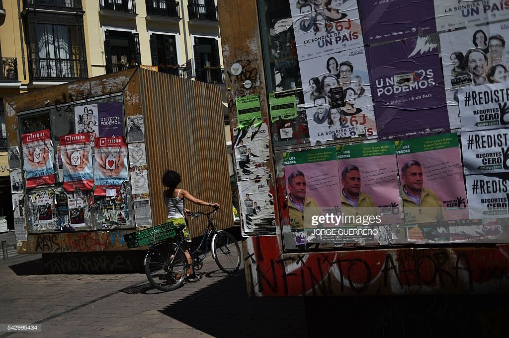 A woman looks at electoral campaign posters of left-wing party Podemos on the eve of Spanish general elections in Madrid on June 24, 2016. Spain votes again on June 26, six months after an inconclusive election which saw parties unable to agree on a coalition government. / AFP / JORGE