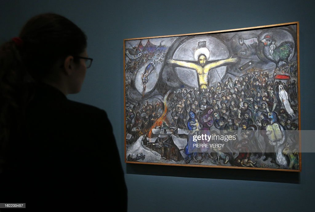 A woman looks at 'Exodus' (1952-1966) painting by Russian-born and naturalized French painter Marc Chagall, during an exhibition entitled 'Between war and peace', on February 20, 2013 at the Museum of Luxembourg in Paris. The event will be held from February 21 until July 21, 2013. AFP PHOTO PIERRE VERDY