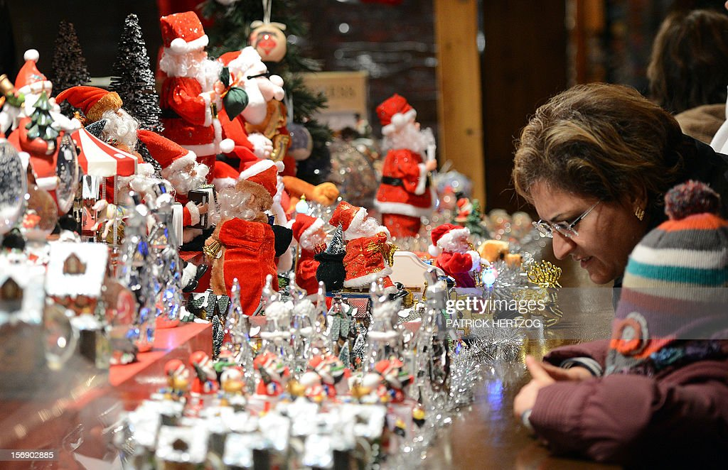A woman looks at figurines displayed at Strasbourg's Christmas market, one of the largest and one of the eldest French Christmas markets, on November 24, 2012 in Strasbourg, eastern France, on the event's opening day. With over 300 market chalets, Strasbourg attracts over 1.6 million visitors during the Christmas season.