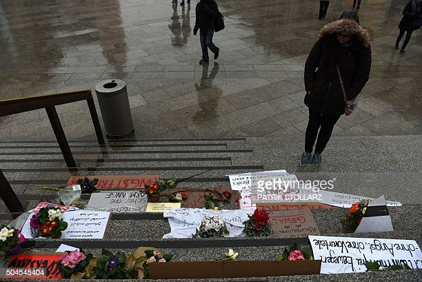A woman looks at flowers and letters of protest that are laid down on the steps of the Cathedral in front of the Cologne main train station in...