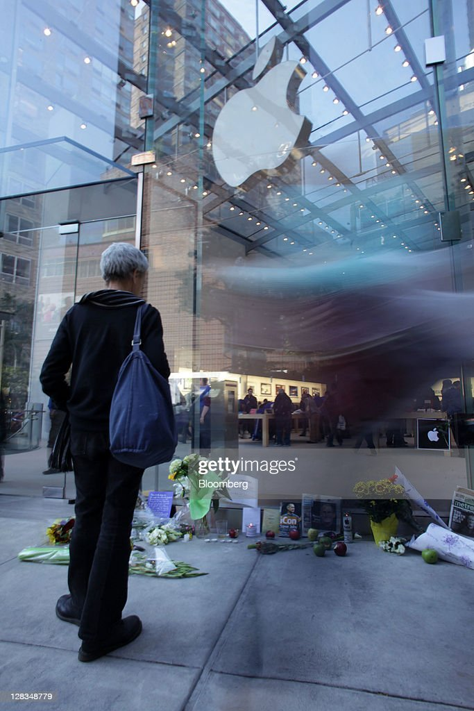 A woman looks at flowers and messages at a memorial for Steve Jobs, co-founder and former chief executive officer of Apple Inc., outside an Apple store in New York, U.S., on Thursday, Oct. 6, 2011. Jobs, who built the world's most valuable technology company by creating devices that changed how people use electronics and revolutionized the computer, music and mobile-phone industries, died on Oct. 5. He was 56. Photographer: Stephen Yang/Bloomberg via Getty Images