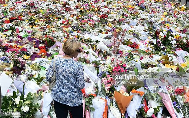 A woman looks at flowers at a makeshift memorial near the scene of a fatal siege in the heart of Sydney's financial district on December 17 2014...