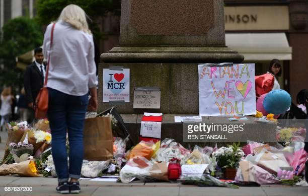 TOPSHOT A woman looks at flowers in Albert Square in Manchester northwest England on May 24 placed in tribute to the victims of the May 22 terror...