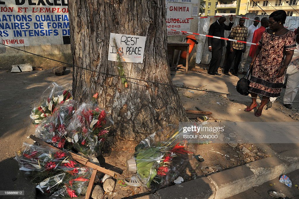 A woman looks at flowers laid at the bottom of a tree on January 2, 2013 in the street of Abidjian where at least 60 persons died in a stampede among crowds gathered for celebratory New Year's Eve fireworks that also left dozens injured. Ivory Coast began today three days of national mourning.