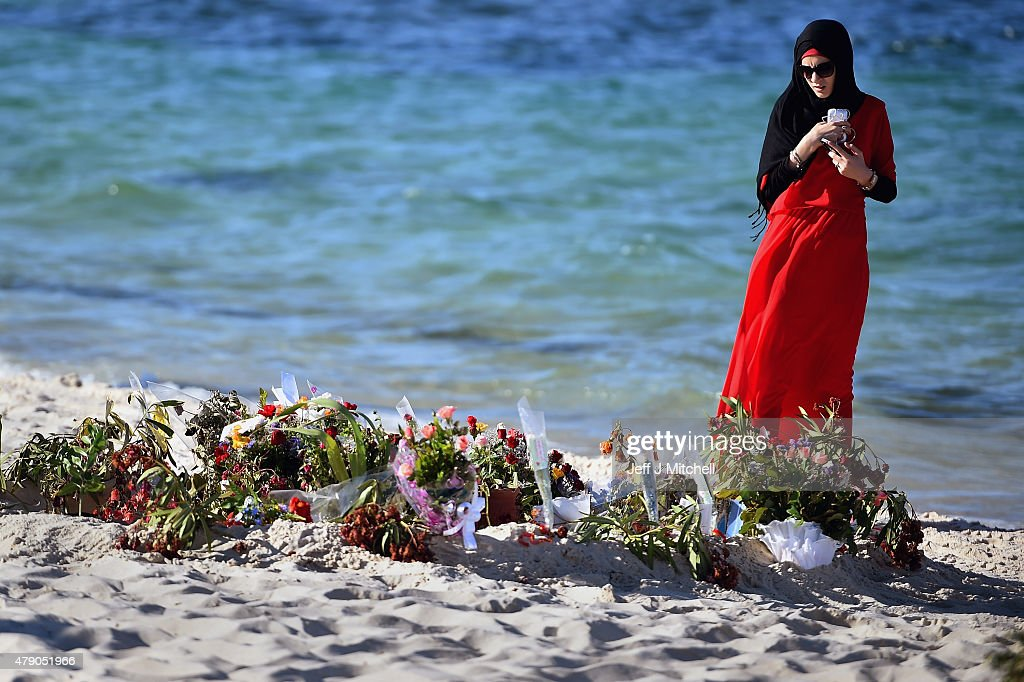 A woman looks at flowers laid on Marhaba beach in Sousse where 38 people were killed in last Fridays terror attack on June 30 2015 in Sousse Tunisia...