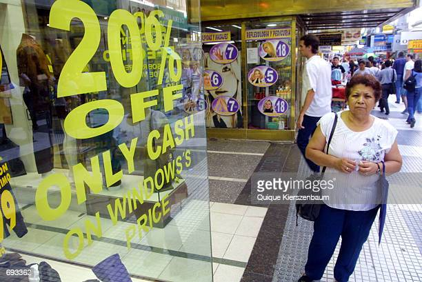 A woman looks at goods in a shop January 12 2002 in one of the Buenos Aires'' wealthiest shopping districts With the new devaluation of the peso...