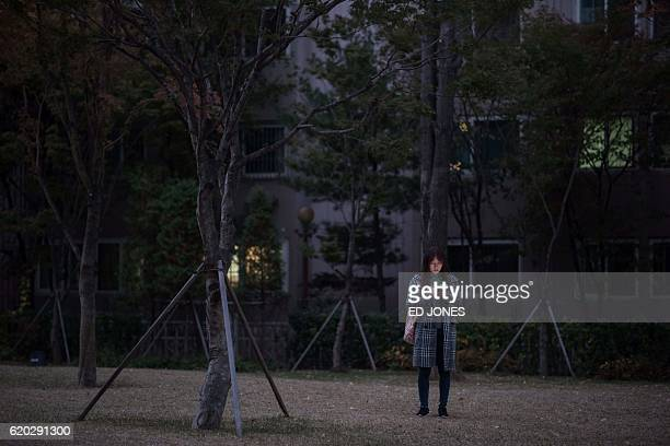 A woman looks at her mobile phone as she stands outside an apartment block in Seoul on November 2 2016 / AFP / Ed Jones