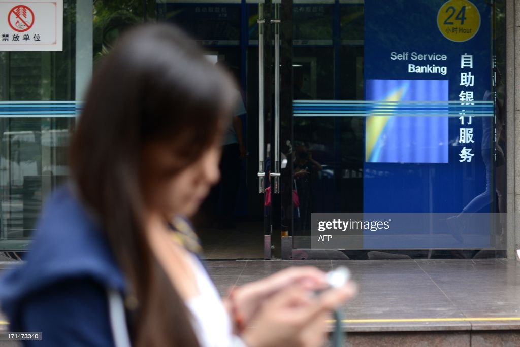 A woman looks at her mobile phone as she walks past a bank in Beijing on June 25, 2013. Chinese shares tumbled 3.80 percent on June 25, extending the previous day's hefty losses as dealers fret over a liquidity crisis in the country's banking system that has squeezed lenders.