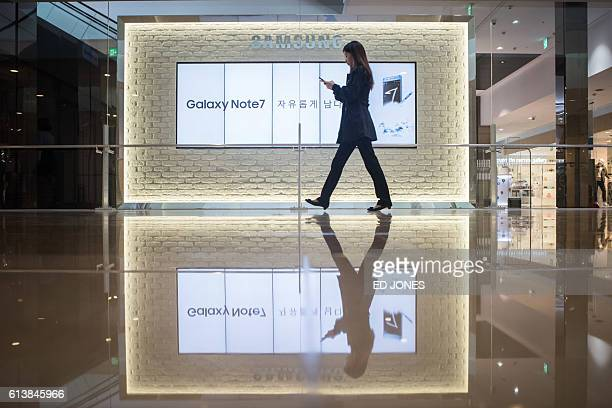 A woman looks at her mobile phone as she walks past advertisements for Samsung's Galaxy Note 7 device at a Samsung store in the Gangnam district of...