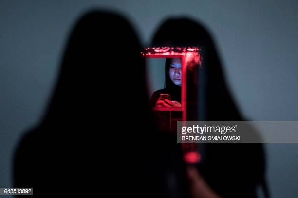 A woman looks at her phone while viewing the Love Forever room during a preview of the Yayoi Kusama's Infinity Mirrors exhibit at the Hirshhorn...