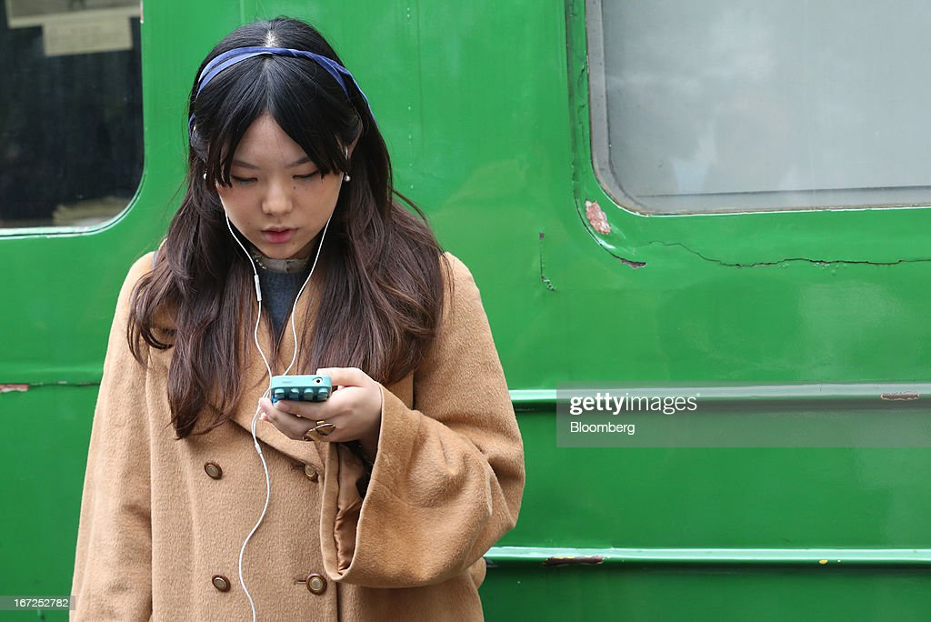 A woman looks at her smartphone outside a train station in Tokyo, Japan, on Sunday, April 21, 2013. The number of smartphone subscribers in Japan surged to 37 percent of all contracts as of March 31 from 3 percent three years earlier, according to Tokyo-based MM Research Institute Ltd. Photographer: Yuriko Nakao/Bloomberg via Getty Images