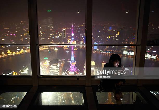 A woman looks at her smartphone while sitting on the floor at the observation deck of the Shanghai World Financial Center as buildings stand...