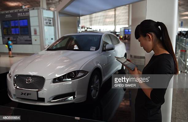 A woman looks at her tablet computer beside a stand for luxury cars at the airport in Beijing on July 13 2015 China's total trade slumped in the...
