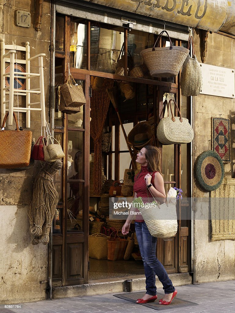 Woman looks at items outside shop : Stock Photo