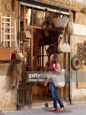 Woman looks at items outside shop