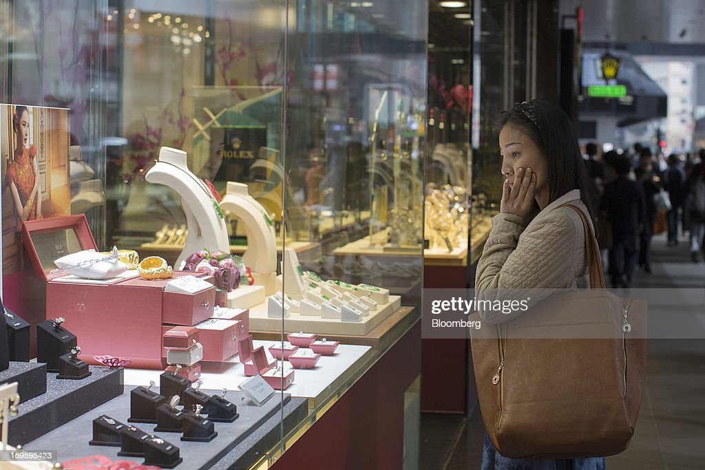 A woman looks at jewelry displayed in the window of a Chow Tai Fook Jewellery Group Ltd. store in the Central district of Hong Kong, China, on Wednesday, Jan. 16, 2013. Chow Tai Fook Jewellery, the world's biggest jeweler by market value, posted an 8 percent drop in third-quarter same-store sales as Chinese shoppers curbed spending amid a slower economy. Photographer: Jerome Favre/Bloomberg via Getty Images