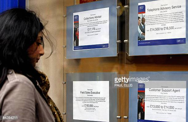 A woman looks at job advertisements in the window of a recruitment agency in Manchester northwest England on January 12 2009 Prime Minister Gordon...