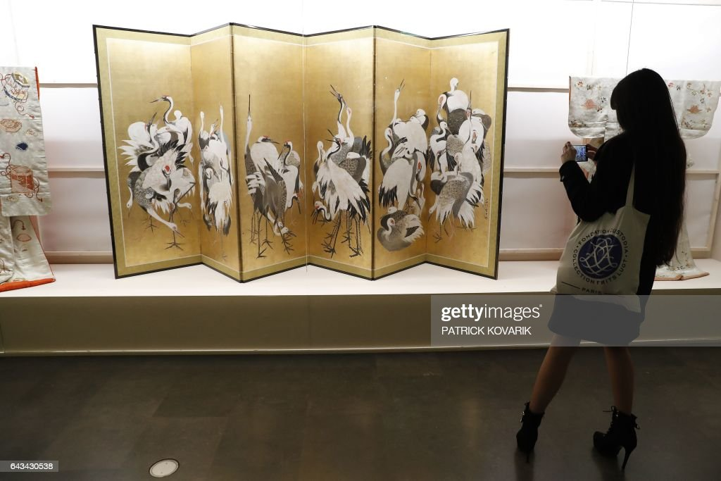 A woman looks at kimonos and a folding screen during the inauguration of the exhibition 'Kimono - Au bonheur des dames' at the Guimet museum in Paris, on February 21, 2017. The exhibition will run from February 22 to May 22, 2017. / AFP / PATRICK