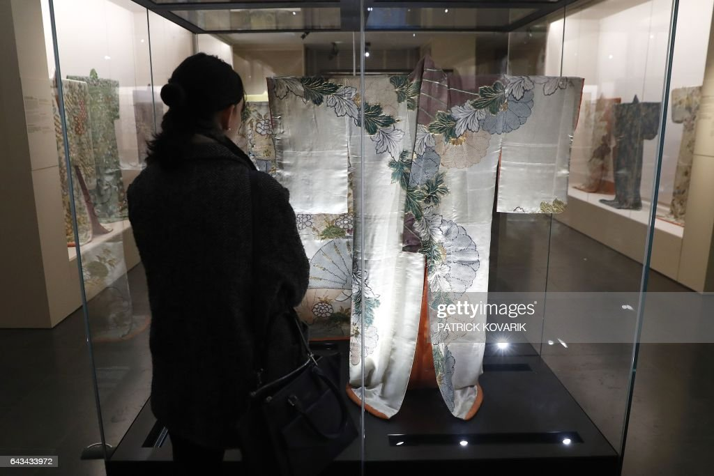 A woman looks at kimonos during the inauguration of the exhibition 'Kimono - Au bonheur des dames' at the Guimet museum in Paris, on February 21, 2017. The exhibition will run from February 22 to May 22, 2017. / AFP / PATRICK