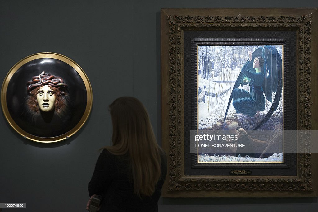 A woman looks at 'La mort et le fossoyeur' by Carlos Schwabe (R) and 'Bouclier avec le visage de meduse' (L) by Arnold Bocklin during the exhibition 'The Angel of the Odd. Dark Romanticism from Goya to Max Ernst' at the Orsay museum in Paris, on March 4, 2013. The exhibition will run from March 5 until June 9, 2013.