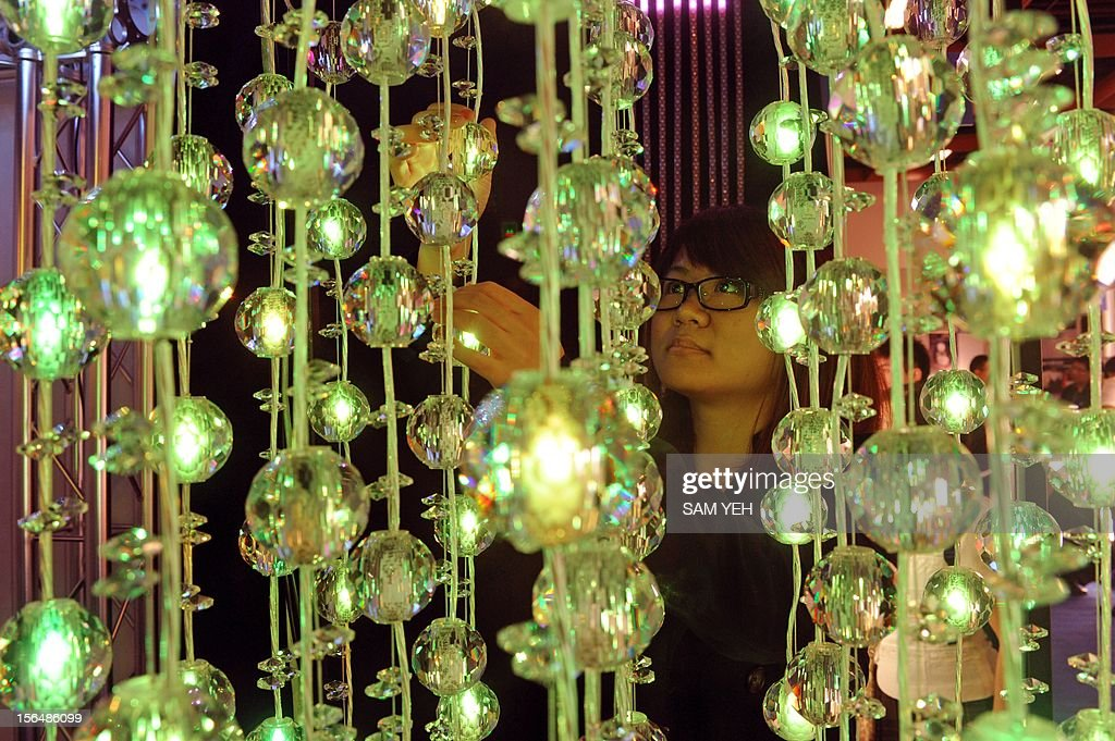 A woman looks at LED lights during a building materials fair at the World trade Center in Taipei on November 16, 2012. More then 1,200 booths take part in this four-day show between November 16 to 19. AFP PHOTO / Sam Yeh