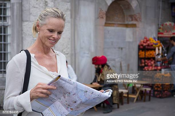 Woman looks at map, colourful street scene