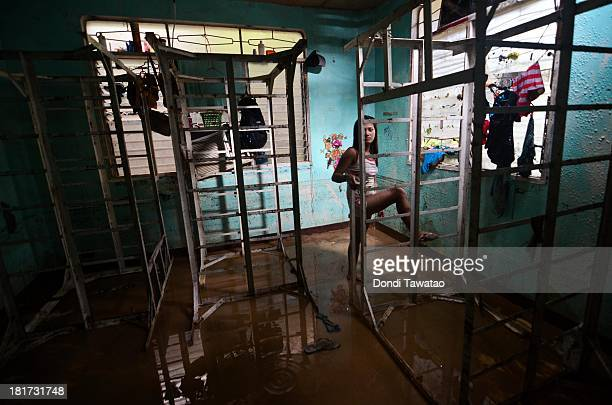 A woman looks at mud and debris inside her apartment after three days of monsoon rains triggered flashfloods and landslides on September 24 2013 in...