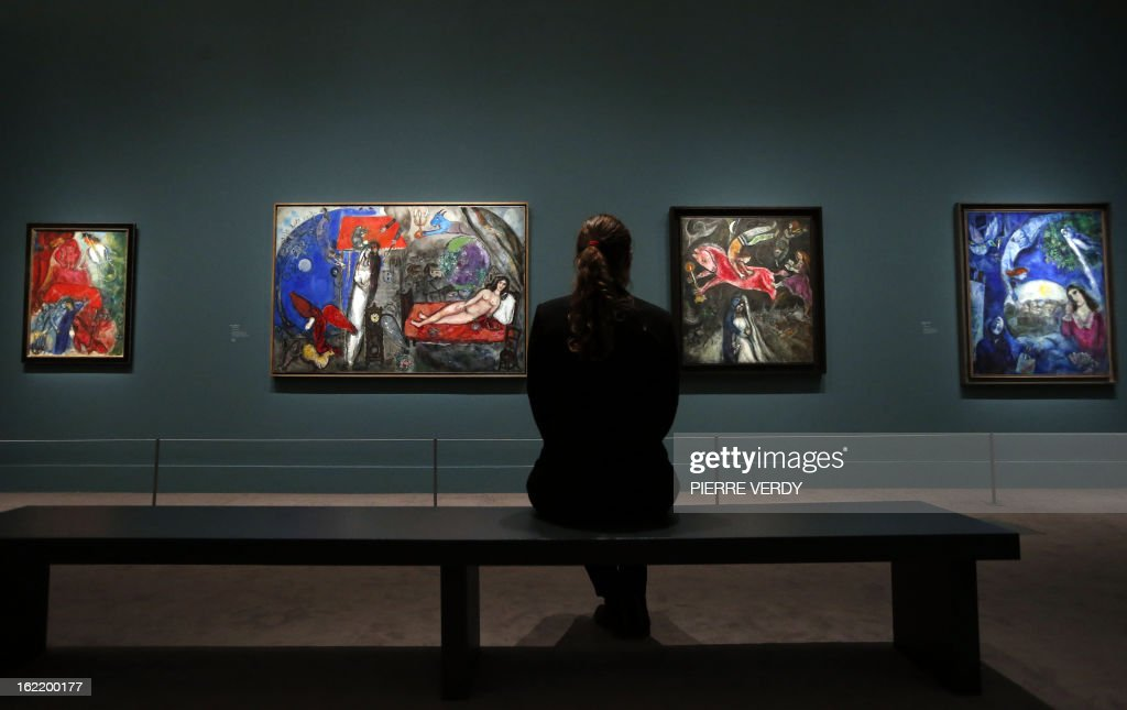 A woman looks at painting by Russian-born and naturalized French painter Marc Chagall, during an exhibition entitled 'Between war and peace', on February 20, 2013 at the Museum of Luxembourg in Paris. The event will be held from February 21 until July 21, 2013. AFP PHOTO PIERRE VERDY