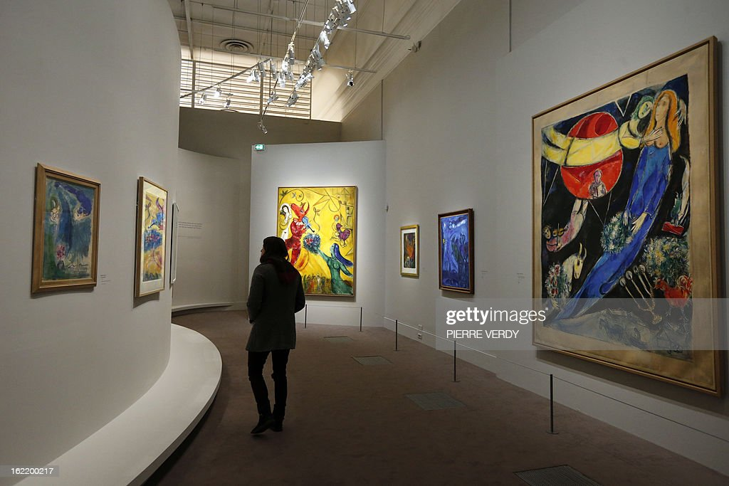 A woman looks at painting by Russian-born and naturalized French painter Marc Chagall, during an exhibition entitled 'Between war and peace', on February 20, 2013 at the Museum of Luxembourg in Paris. The event will be held from February 21 until July 21, 2013.