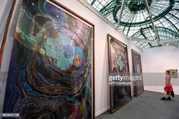 A woman looks at paintings by German artist Kerstin Bratsch as she visits the Paris International Contemporary Art Fair at the Grand Palais in Paris...