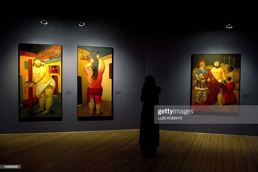 A woman looks at paintings of the exhibition 'Via Crucis, the passion of Christ' of Colombian artist Fernando Botero, on October 8, 2013, in Cali, department of Valle del Cauca, Colombia. Botero was the curator of his own exhibition, which is composed of 27 oil paintings and 34 drawings combining traditional aspects of Catholicism and the modern world.