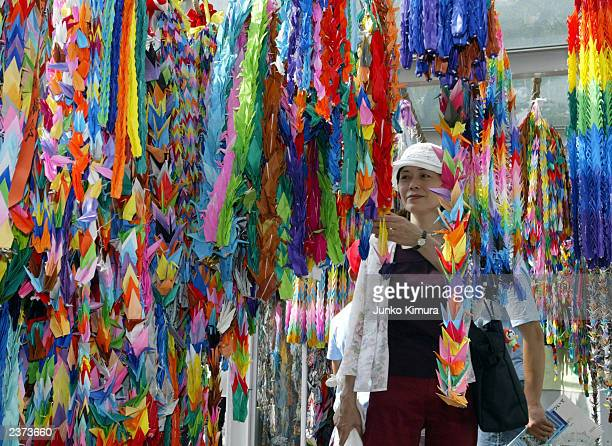 A woman looks at paper birds symbolizing peace on the 58th anniversary of the dropping of the first atomic bomb August 6 2003 in Hiroshima Japan The...