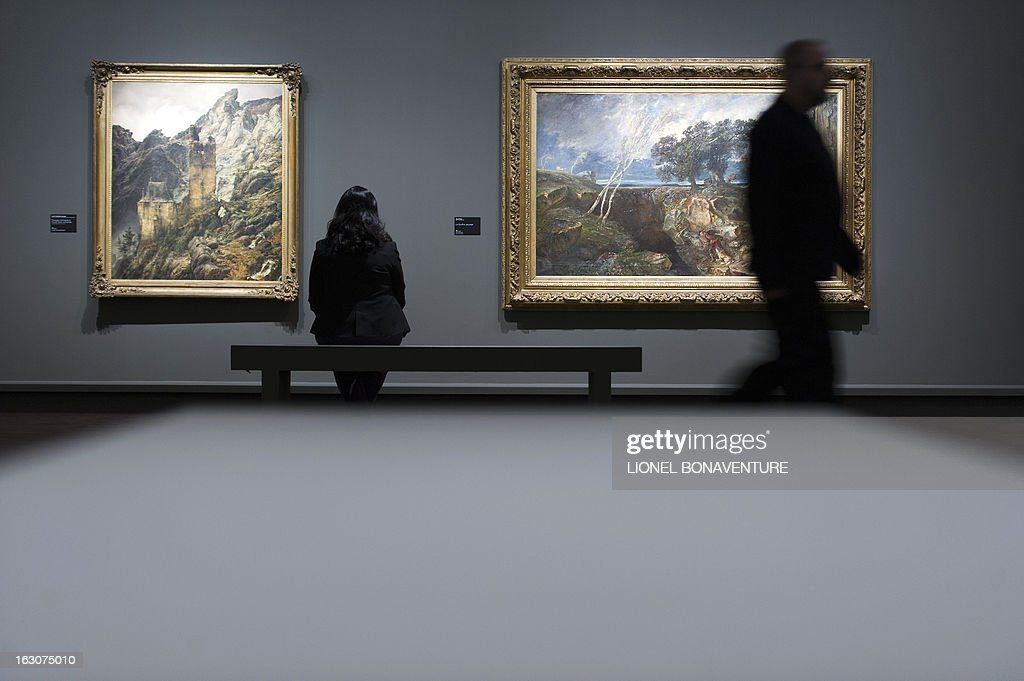 A woman looks at 'Paysage montagneux : ruines dans une gorge' (L) painting by Carl Friedrich Lessing and 'Le gouffre' painting by Paul Huet, displayed during the exhibition 'The Angel of the Odd. Dark Romanticism from Goya to Max Ernst' at the Orsay museum in Paris, on March 4, 2013. The exhibition will run from March 5 until June 9, 2013.