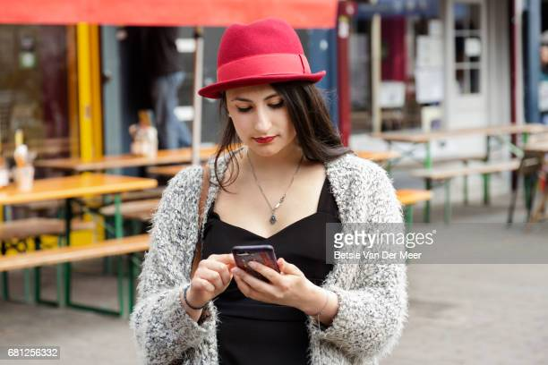 Woman looks at phone, standing in food market.