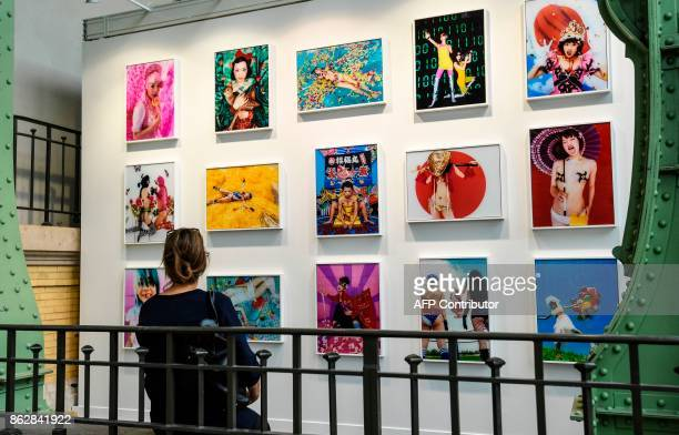 A woman looks at photographs by Japanese photographer Mika Ninagawa as she visits the Paris International Contemporary Art Fair at the Grand Palais...