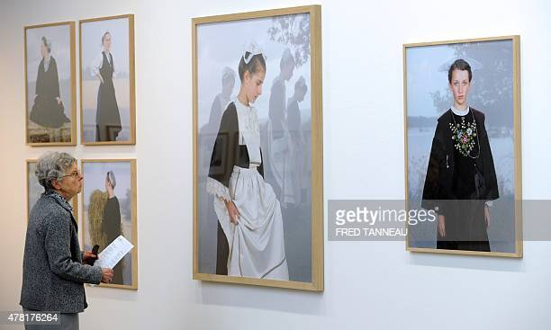 A woman looks at pictures by French photographer Charles Freger during an exhibition on traditional costumes and headdresses in Brittany on June 20...