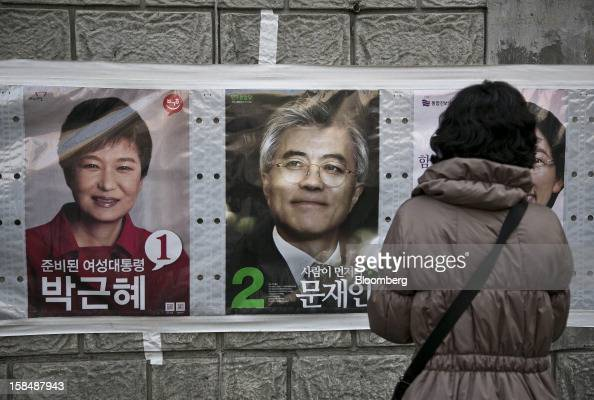 A woman looks at posters of South Korean presidential candidates Park Geun Hye from the ruling New Frontier Party left and Moon Jae In from the main...