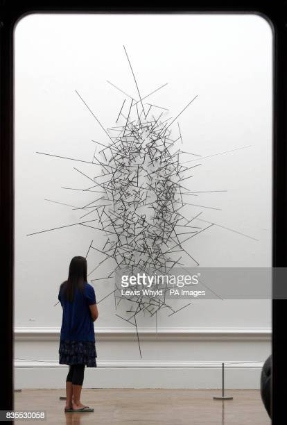 A woman looks at Quantum Void VI a sculpture by Antony Gormley showing at the Royal Academy Summer Exhibition which is being previewed today ahead of...