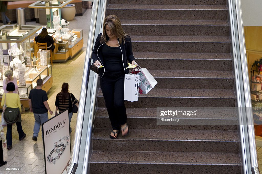 A woman looks at receipts while carrying an Aldo Group Inc. shopping bag and descending stairs at the Fair Oaks Mall in Fairfax, Virginia, U.S., on Monday, Nov. 12. 2012. Sales at U.S. retailers probably fell in October for the first time in four months economists said before a report on Nov. 14. Photographer: Andrew Harrer/Bloomberg via Getty Images