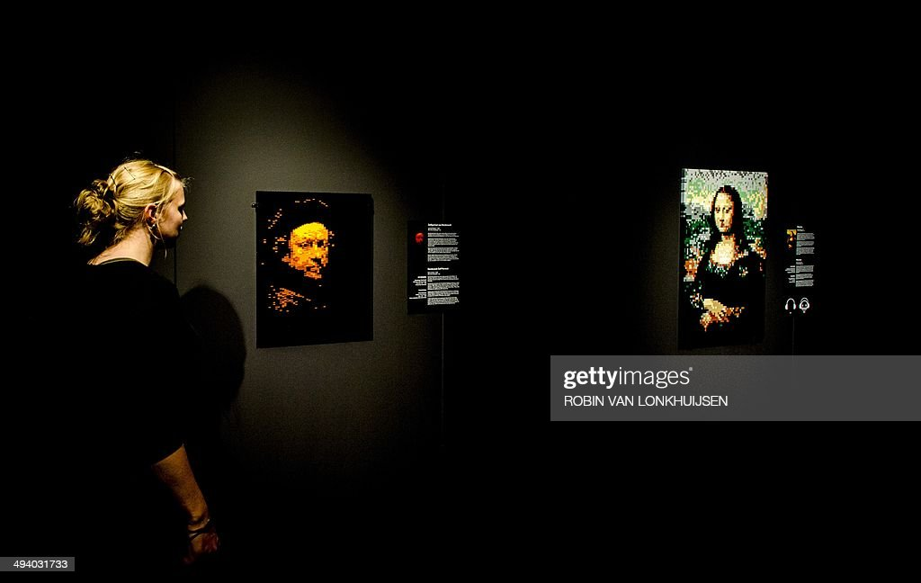A woman looks at replicas of famous paintings made out of Lego bricks by New York-based artist Nathan Sawaya, on display during the exhibition 'The Art of Brick' held at the Amsterdam EXPO in Amsterdam, the Netherlands, on May 27, 2014. The exhibition by New York-based artist Nathan Sawaya presents more than 70 artworks open to the public as of May 29, 2014. AFP PHOTO / ANP / ROBIN VAN LONKHUIJSEN == RESTRICTED TO EDITORIAL USE, TO ILLUSTRATE THE EVENT AS SPECIFIED IN THE CAPTION ==