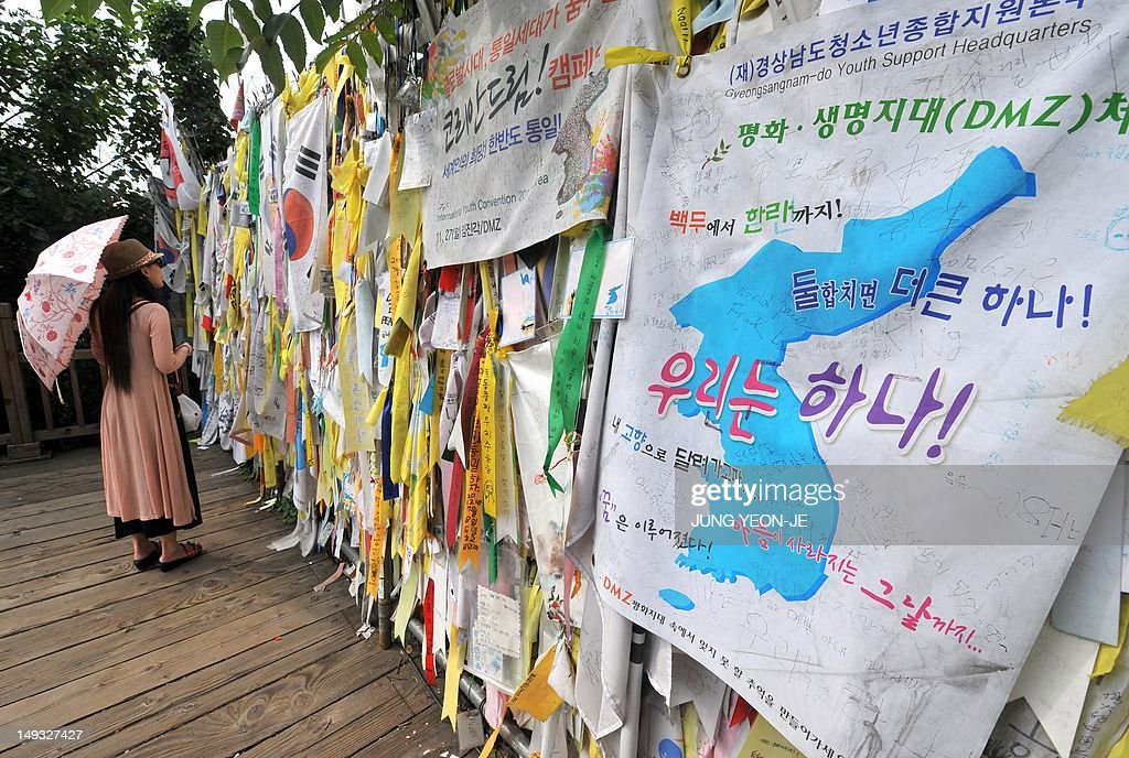 A woman looks at 'reunification ribbons' displayed on a military barbed wire fence at Imjingak peace park in Paju, near the demilitarized zone dividing the two Koreas on July 27, 2012, on the day of the 59th anniversary of signing the Korean War armistice. The armistice agreement on July 27, 1953 brought three years of active combat in the Korean War to a halt, but the two Koreas are still technically at war as no formal peace treaty was signed.