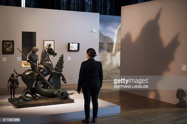 A woman looks at 'Saint Georges and the Dragon' a sculpture by Salvador Dali part of the 'Lieux Saints partages' exhibition held at the at the Museum...