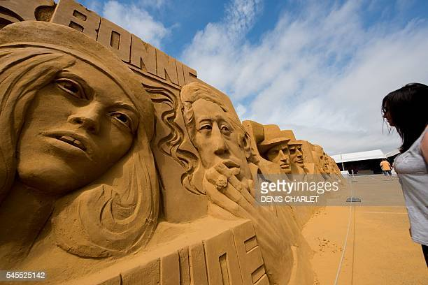 A woman looks at sand sculptures of French singers Serge Gainsbourg and Brigitte Bardot on the Touquet Beach northern France on July 8 2016 Around...