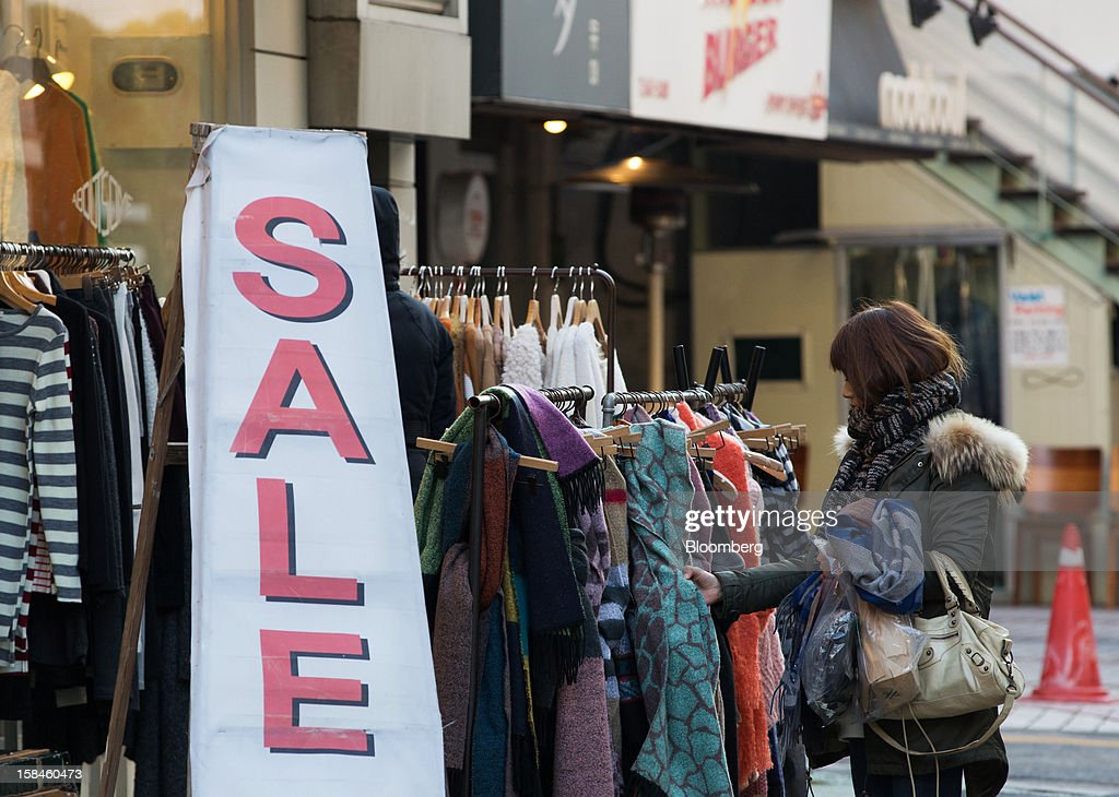 A woman looks at scarves on sale at a store on Garosugil street in the Gangnam district of Seoul, South Korea, on Saturday, Dec. 15, 2012. South Koreans vote on Dec. 19 to replace President Lee Myung Bak, whose five-year term ends in February. Photographer: SeongJoon Cho/Bloomberg via Getty Images