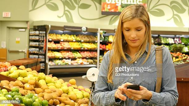 Woman looks at shopping list on smart phone in supermarket