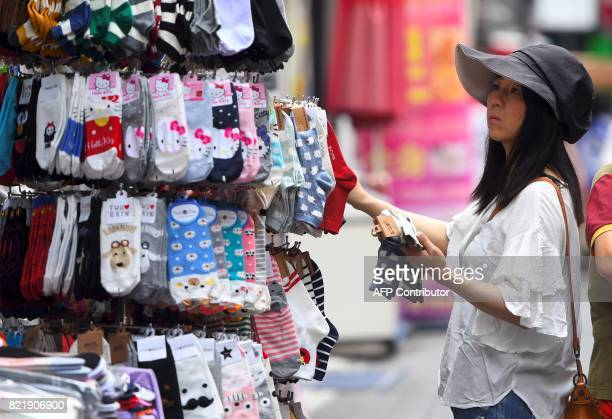 A woman looks at socks for sale at a shopping district in Seoul on July 25 2017 South Korea's economy is set to grow at its fastest rate in three...
