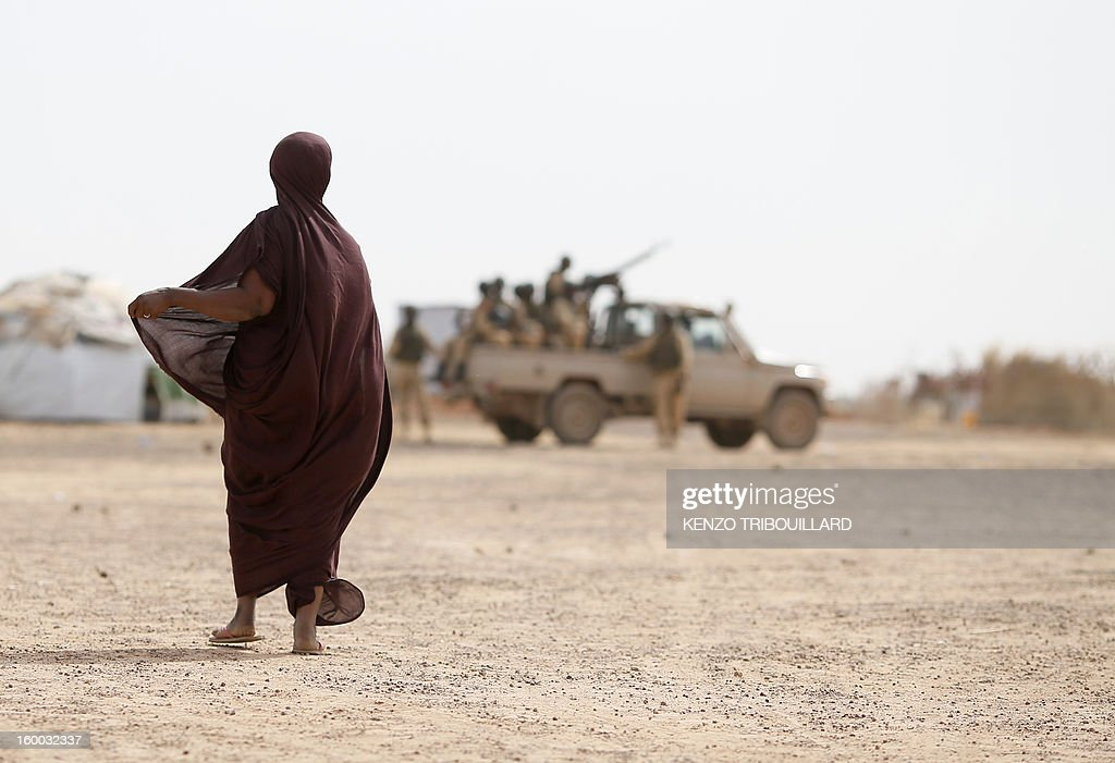 A woman looks at soldiers on January 24, 2013 in a refugee camp set in Menteao, near the Malian border. The conflict in Mali has caused nearly 150,000 people to flee the country, while about another 230,000 are internally displaced, the UN humanitarian agency said on January 15, 2013. According to OCHA, the UN High Commissioner for Refugees has registered 144,500 refugees in neighbouring countries -- 54,100 in Mauritania, 50,000 in Niger, 38,800 in Burkina Faso and 1,500 in Algeria. AFP PHOTO KENZO TRIBOUILLARD