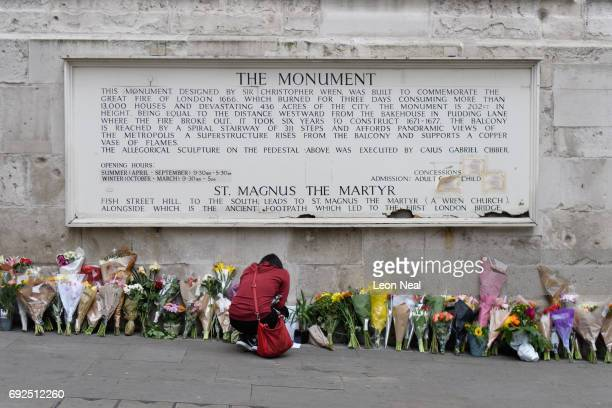 A woman looks at some of the floral tributes at Monument near London Bridge following the June 3rd terror attack on June 5 2017 in London England...