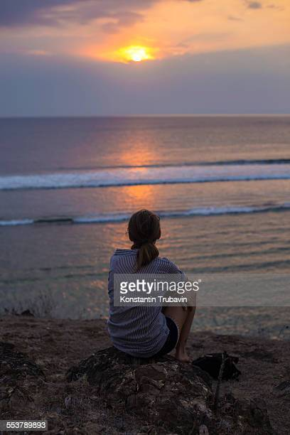 Woman looks at sunset in the ocean.